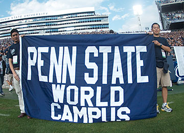 Two alumni holding the Penn State World Campus banner at Beaver Stadium