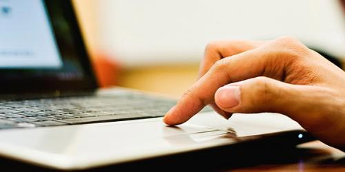 Person's hand on a computer touchpad
