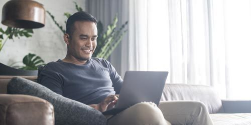 Man sitting on a couch with a laptop